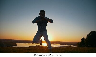 Sportsman is engaged in capoeira in the background of an orange sunset, slow-motion
