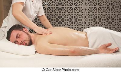 Sportsman is receiving back massage in Spa room. - Sportsman...