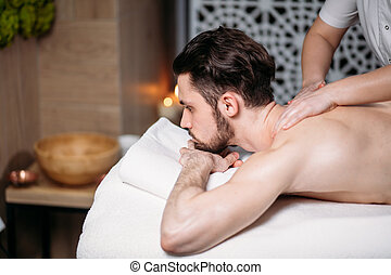 sportsman is receiving back massage in spa room - sportsman...