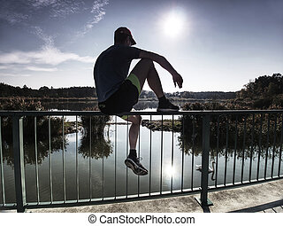 Sportsman is sitting on handrail in the park. Feet of jogging man
