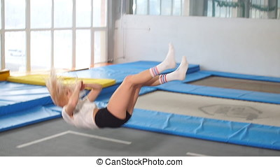 Sportsman jumping on a trampoline and doing split indoors. -...