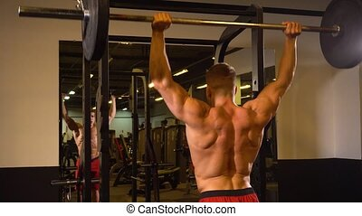 Sportsman lifting barbell near mirror - Back view of...