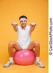 Sportsman man on fitness ball doing exercises with small dumbbells