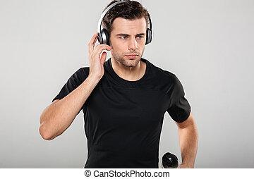 sportsman, musik lyssna, stående, allvarlig, stilig