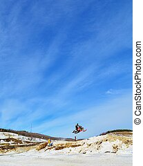 sportsman on snowmobile jumping a background of blue sky with clouds