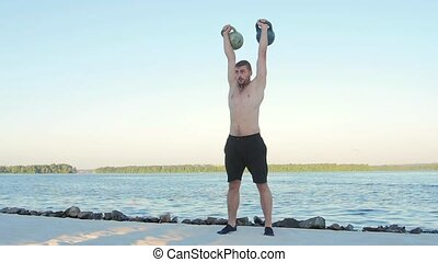 Sportsman picks up a dumbbell. Slow motion