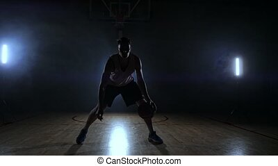 Sportsman playing basketball in basketball court.