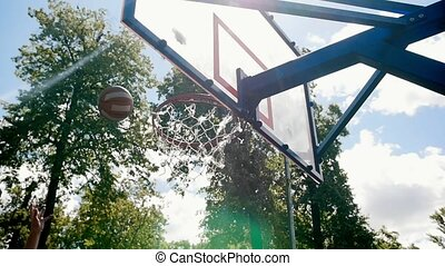 Sportsman playing basketball on the court outdoors trying to...
