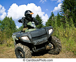 Sportsman riding quad bike at the summer forest