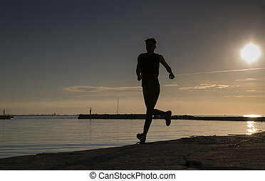 Sportsman run along the sandy beach late evening