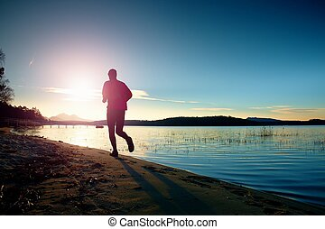 Sportsman running at amazing summer sunset at the beach in sport and healthy lifestyle concept