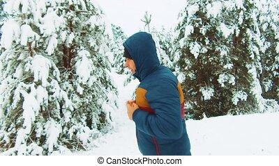 Sportsman Running Through Snowy Forest. Athlete man is...