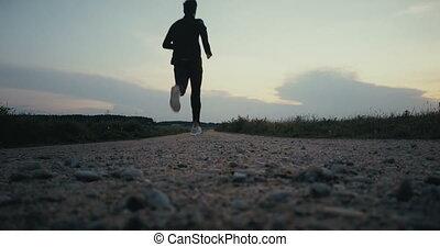 Sportsman running towards rural sunset panorama. Freedom....