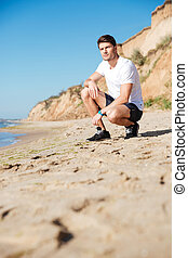 Sportsman sitting alone on the beach