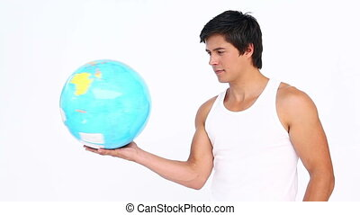 Sportsman spinning a globe against white background