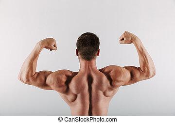 Sportsman standing showing biceps.