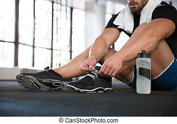 Sportsman ties his sneakers - Sportsman ties his black...