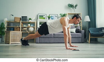 Sportsman touching smartphone screen then practising plank...