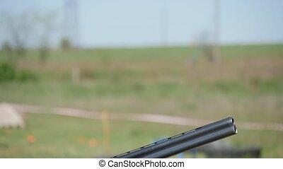 Sportsman training skeet shooting in a green field on a...