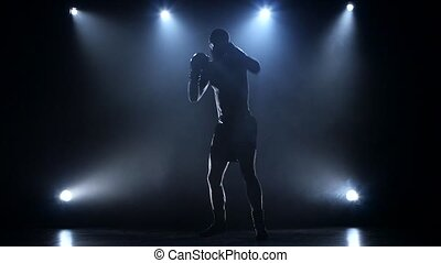 Sportsman trains to become a boxing champion, spotlight on a dark background in the studio, doing blows and moves in different directions, body naked torso and wearing shorts, slow motion