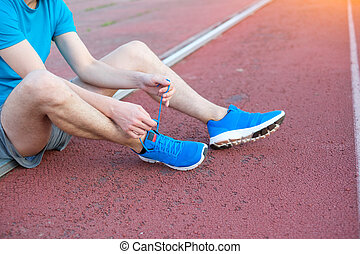 Sportsman tying his shoelaces ready for the race