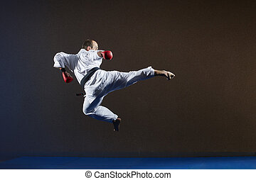 Sportsman with a black belt and red overlays on his hands beats a kick in the jump