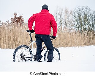 Sportsman with mountain bike lost in snow. Winter in the field.