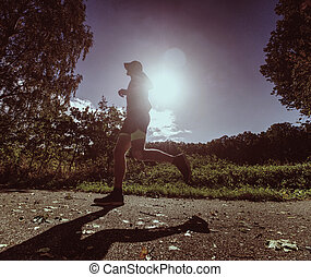 Sportsman within exercise in park. Man is running or jumping