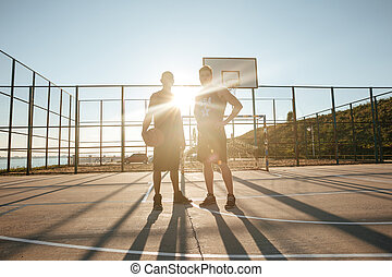 Sportsmen standing with basketball at the playgroung