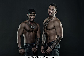 Sportsmen with muscular chest and belly. African and hispanic men with sexy bare torso. Men with fit tattooed body. Fashion models with tattoo in jeans. Sport with fitness and bodycare, vintage filter