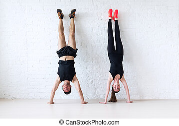 sportsmen woman and man doing a handstand against wall...