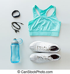 sport, fitness, healthy lifestyle and objects concept - close up of female sports clothing, heart-rate watch, earphones and bottle set