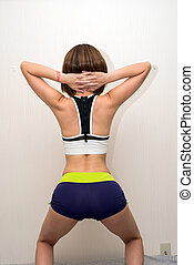 Sportswear woman squatting - Back view of sportswear woman ...