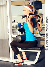 sportswear - Young sporty woman doing exercises in the gym ...