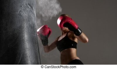 Sportswoman boxer knocks out of the punching bag. Slow motion