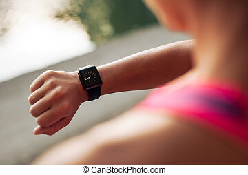 Sportswoman checking time on smartwatch - Close up image of ...