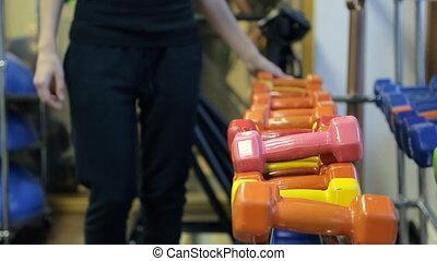 Sportswoman choose dumbbells to train in sport gym