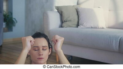 Brunette sportswoman in black top does crunches near sofa in spacious living room during covid lockdown closeup slow motion