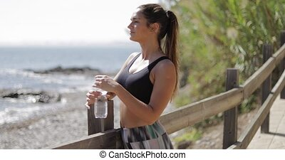 Sportswoman drinking on shore - Pretty young model in...