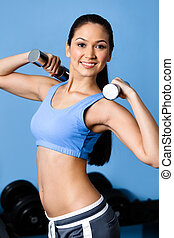 Sportswoman exercises with dumbbells