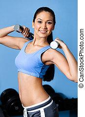 Sportswoman exercises with dumbbells