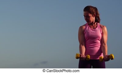 Sportswoman Exercising with Weights on the Beach