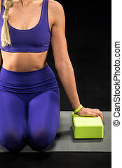 Sportswoman exercising with yoga block