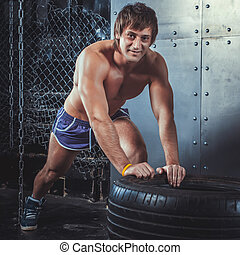 Sportswoman. Fit sporty man resting after exercising push ups on tire strength power training looking at camera concept crossfit fitness workout sport and lifestyle.