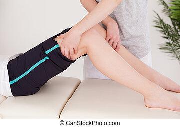 Sportswoman having a leg massage