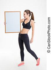 Sportswoman holding blank board
