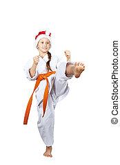 Sportswoman in a cap of Santa Claus hits a kick leg