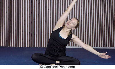 Sportswoman is doing yoga exercises in modern gym.