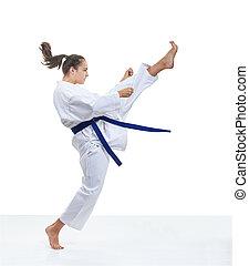 Sportswoman is training a kick in karategi