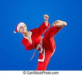 Sportswoman is training kick leg in the suit of Santa Claus